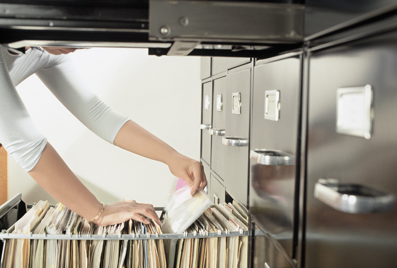 ca. 2000 --- Woman Pulling Files from File Cabinet --- Image by © Royalty-Free/Corbis